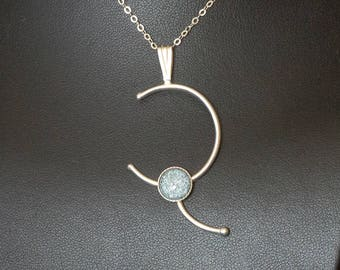 A simple, yet very elegant pendant with a single kiln fired enamel at its centre.