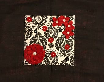 This Canvas Wrapped with Black and White Canvas Fabric adorned with Red Felt Flowers.