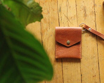 Brown Leather Cardholder with snap cover and wrist strap .