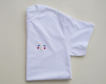 Large hand embroidered primary face on white t-shirt