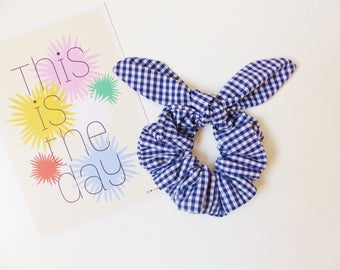 With a bow tie / hair tie / scrunchie elastic gingham with a bow