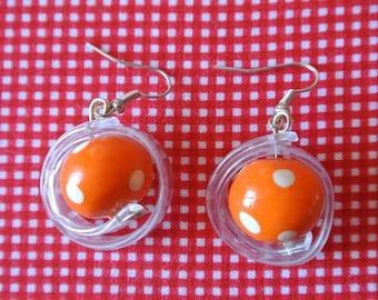 Orange hoop earrings has white dots