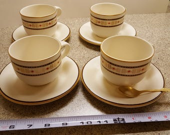 Gold rimmed coffee cup with saucers and spoon