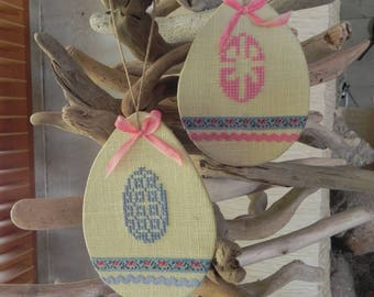 Two Easter eggs hanging yellow linen