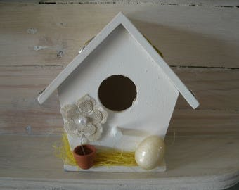 small yellow decorative birdhouse and linen