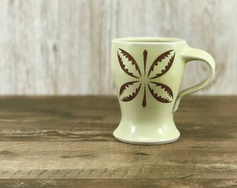 Curvy mug with creamy yellow glaze and mod design