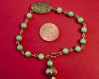 A Vintage Green Wooden Bead Bracelet with a Green Glass Centerpiece