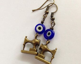 S E W - S T I T CH Y- Brass sewing machine earrings with blue and white bullseye glass beads.