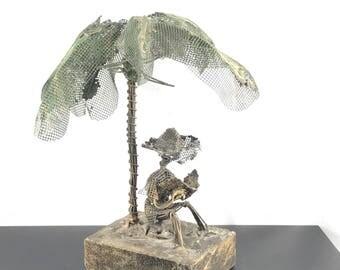 George Blackett Barbados Sculpture. 1982. Metal sculpture man reading palm tree. Wire art.