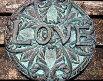 A love wall decor.  Cast out of cement and recycled newspaper.