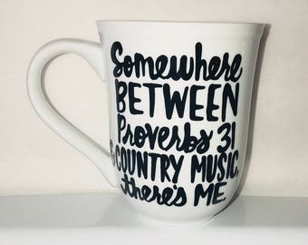Somewhere between Proverbs 31 country music theres me- funny coffee mug- christmas gift- trap music gangster rap white elephant gift funny