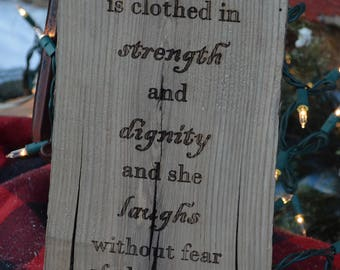 Proverbs 31:25 engraved in 100 yr old barnwood.