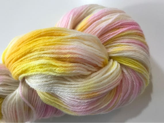 Hand dyed wool yarn in pink, yellow and white.