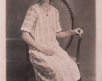 Studio Photograph of a Young Woman Sitting on a Chair. - Postcard - Blank.