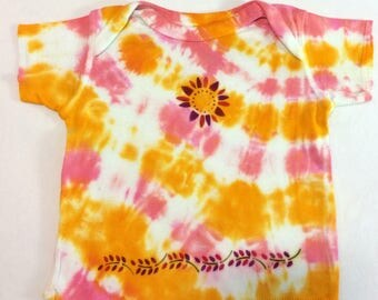 Infant 12 month short sleeve pull over hand tie dyed shirt with dyed flowers on front and bottom on the shirt