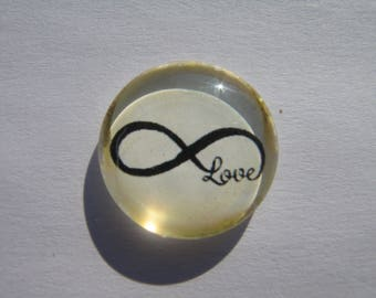 Cabochon 20 mm with a drawing of the infinity sign on a beige background