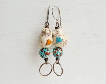 Songbird - subtly mismatched artisan-bead bird earrings in aqua, orange and cream with polymer and glass beads - Songbead UK, narrative