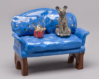 """Ceramic sculpture, clay hand built """"Scruffy dog"""" on sofa with present."""