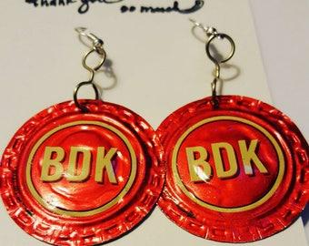 Red upcycled Brew Dr Kombucha Bottle-cap earrings.
