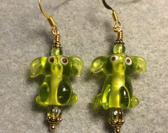 Translucent olive green lampwork sitting elephant bead earrings adorned with olive green Czech glass beads.