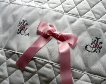 White quilt with embroidered initial