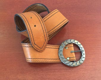 Tan leather belt with stitches and metal belt
