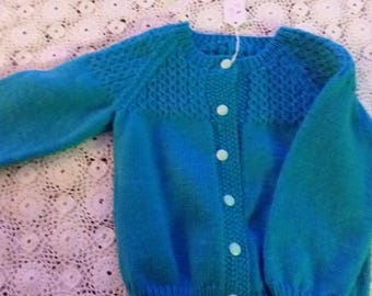 Blue girl's cardigan with mock cable stitch.