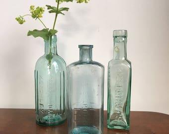Set of three embossed vintage glass bottles - old kitchen and medical glass bottles