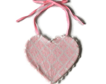 White heart on pink ground shaped bib