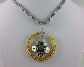 Necklace: The Empty Child; silvery gas mask and gold glass beads on silver + gold braided cord; for fans of Doctor Who