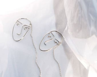 Silver earring (one from the set) with faces