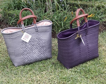 Of plastic woven bag with lining and leather handles