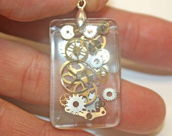 Beautiful steampunk pendant w/vintage watch parts in crystal clear resin.