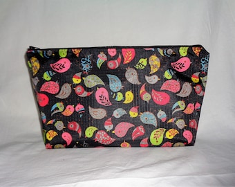 """Toiletry bag in coated canvas """"colorful birds"""" on a black background."""
