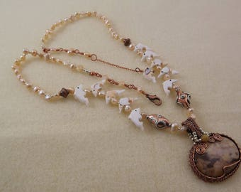 picture jasper and antiqued copper pendant on a necklace of pearls, carved shell dolphins with copper and sterling silver focal beads