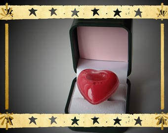 a heart-shaped red opaque liquid filled glass globe mounted on a ring holder