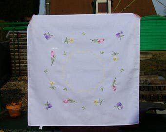 tablecloth has the embroidered pastel colors