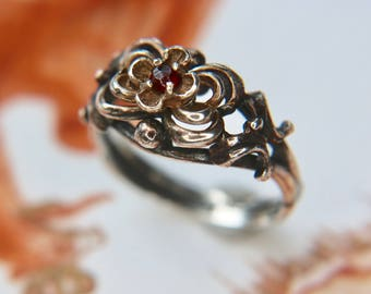 Antique handcrafted silver ring with a flower layered ring head enchanted with a facetted Garnet