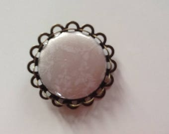Bronze color metal brooch with beige fabric badge with white flowers