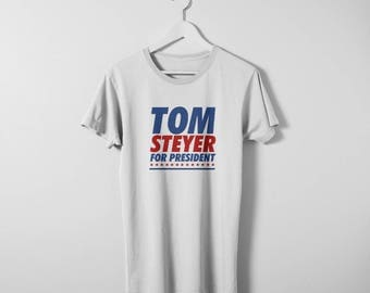 Tom Steyer A New Time for Greatness t-shirt. Available in men's and women's sizes. Printed on a comfy cotton Bella Canvas Tee.