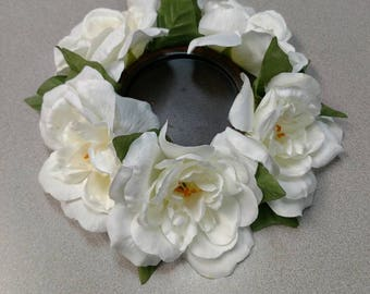 Candle Holder with wood center surrounded with beautiful white flowers.