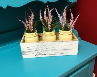Yellow mason jars and wooden crate