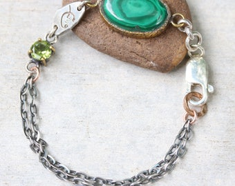 Oval malachite bracelet in brass bezel setting with round peridot secondary gemstone and oxidized sterling silver double chain