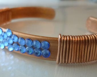 Impressive Empress copper cuff bracelet is adorned with blue flat back crystals and copper wire