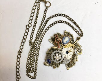 Steampunk style bronze leaf with vintage accents- pendant necklace, cameo,key ,gears ,dial
