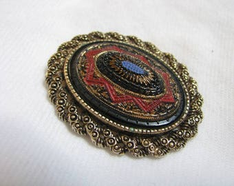 Gold tone oval pin/pendan broocht with black blue & red accents.  Old Vienna by Sarah Coventry