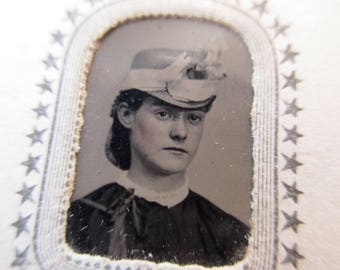 antique tintype with paper frame - young woman, rosy cheeks, hat