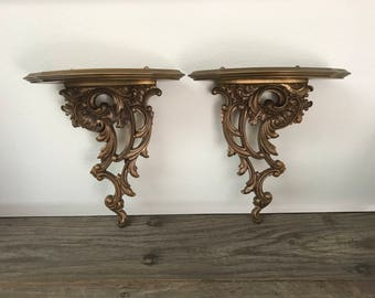 A pair of two Syroco Wood gold ornate scroll wall shelves