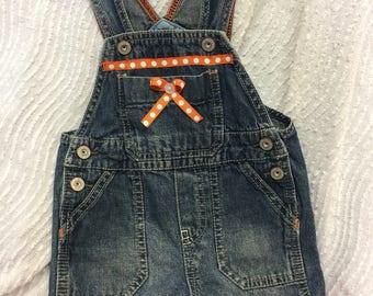 Orange trimmed little girls Oshkosh overall shorts