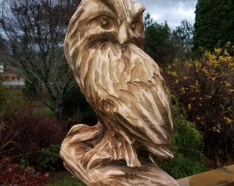 chainsaw carving of owl perched on branch